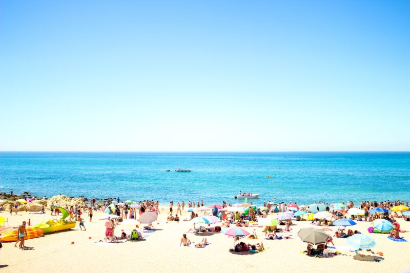seashore with crowding people under blue sky